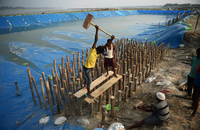 """Indian labourer construct a wooden platform in a temporary pond made of plastic sheeting, into which idols of the Hindu Goddess Durga will be immersed after """"Durga Puja"""" as part of the """"Durga Puja"""" festival, in Allahabad on September 26, 2017. (Photo by Sanjay Kanojia/AFP Photo)"""