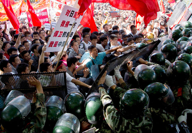 Chinese demonstrators clash with policemen at barricades during an anti-Japanese protests outside the Japanese Embassy in Beijing, on Saturday, September 15, 2012. (Photo by Andy Wong/AP Photo)