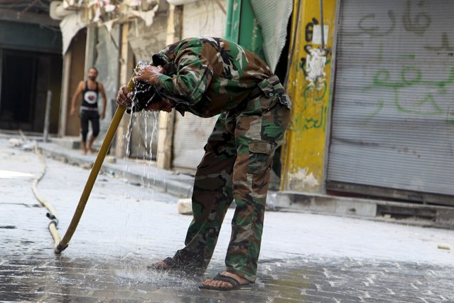 """A """"Free Syrian Army"""" fighter washes his head in Old Aleppo, Syria September 5, 2015. (Photo by Abdalrhman Ismail/Reuters)"""