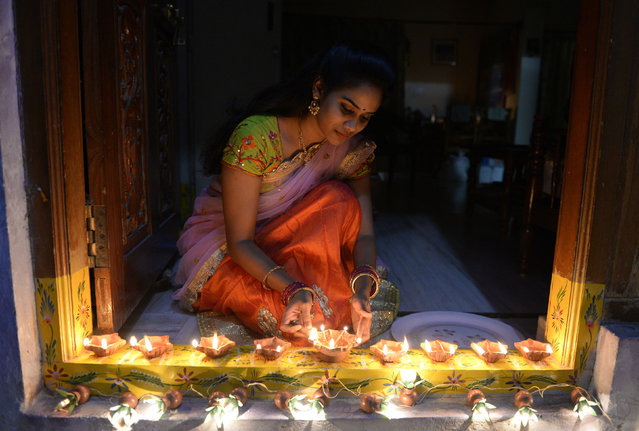 """An Indian woman Nikitha places earthen lamps or """"diyas"""" at the entrance of her home on the eve of Diwali Festival in Hyderabad on October 18, 2017. Diwali, the Hindu festival of lights, marks the triumph of good over evil, and commemorates the return of Hindu deity Rama to his birthplace Ayodhya after victory against the demon king Ravana. (Photo by Noah Seelam/AFP Photo)"""