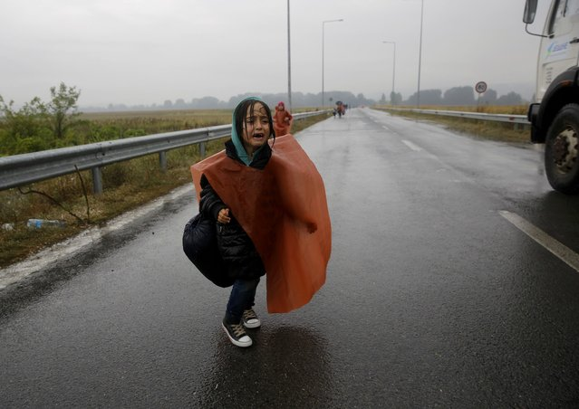 A Syrian refugee girl cries as she walks through a rainstorm towards Greece's border with Macedonia, near the Greek village of Idomeni, September 10, 2015. Most of the people flooding into Europe are refes fleeing violence and persecution in their home countries who have a legal right to seek asylum, the United Nations said on Tuesday. (Photo by Yannis Behrakis/Reuters)