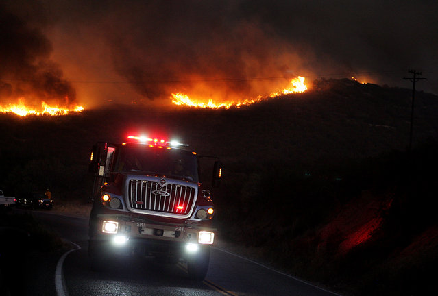 A fire engine drives away from flames on the ridge, east of Silverwood Lake in Crestline, Calif., Sunday, August 7, 2016. (Photo by Terry Peirson/The Press-Enterprise via AP Photo)