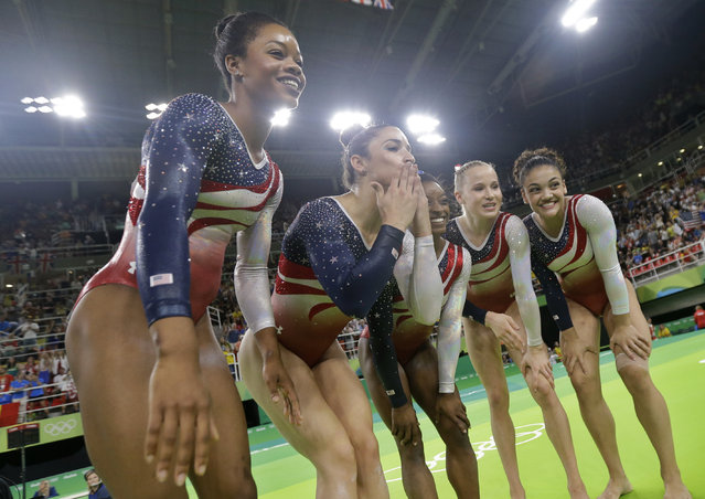 U.S. gymnasts, left to right, Gabrielle Douglas, Aly Raisman, Simone Biles, Madison Kocian, and Lauren Hernandez pose for the camera at the end of the artistic gymnastics women's team final at the 2016 Summer Olympics in Rio de Janeiro, Brazil, Tuesday, August 9, 2016. (Photo by Julio Cortez/AP Photo)