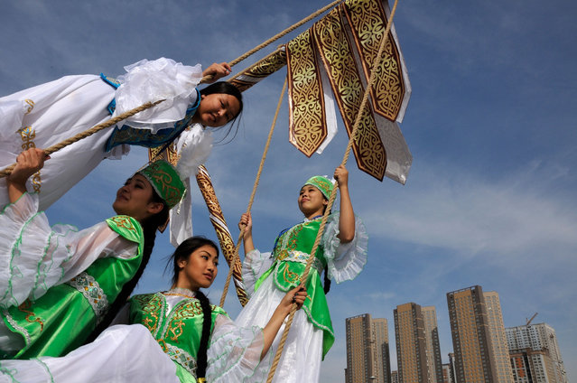Kazakh women wearing traditional costumes play on a swing during celebrations marking the 550th anniversary of Kazakh statehood in central Astana on September 11, 2015. (Photo by Bolat Shaikhinov/AFP Photo)