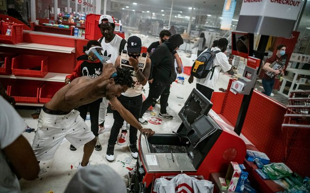 In this Wednesday, May 27, 2020 photo, a looter uses a claw hammer as he tries to break in to a cash register at a Target store in Minneapolis. Rioters ignited fires and looted stores all over the city, as peaceful protests turned increasingly violent in the aftermath of the death of George Floyd. (Photo by Richard Tsong-Taatarii/Star Tribune via AP Photo)
