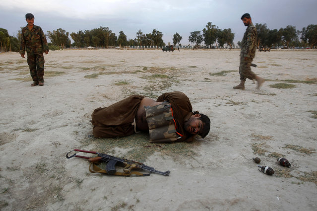 Afghan National Army (ANA) soldiers approach a suicide attacker after his vest was defused in Jalalabad province June 30, 2013. Afghan security forces captured a would-be suicide attacker before he blew himself up in Jalalabad on Sunday. (Photo by Reuters/Parwiz)