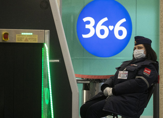A worker of the public transport network wearing a protective face mask guards a security checkpoint at the entrance to the Leningradsky Railway Station amid the ongoing coronavirus COVID-19 pandemic in Moscow, Russia, 19 May 2020. Moscow Mayor Sergei Sobyanin announced a resumption of work of industrial and construction enterprises in Moscow from 12 May on, in accordance with the implementation of measures to support the economy and the social sector, while restrictions imposed to stem the widespread of the SARS-CoV-2 coronavirus which causes the COVID-19 disease will be valid until 31 May 2020. (Photo by Sergei Ilnitsky/EPA/EFE)