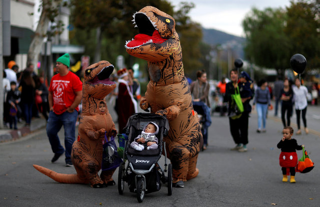 People wearing costumes walk during Halloween in Sierra Madre, California, U.S., October 31, 2017. (Photo by Mario Anzuoni/Reuters)