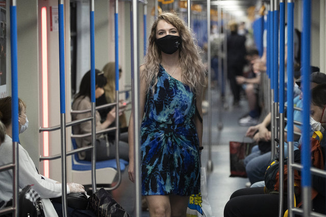 A woman wearing a face mask to protect against coronavirus walks in a carriage of a subway in Moscow, Russia, Wednesday, June 10, 2020. (Photo by Pavel Golovkin/AP Photo)