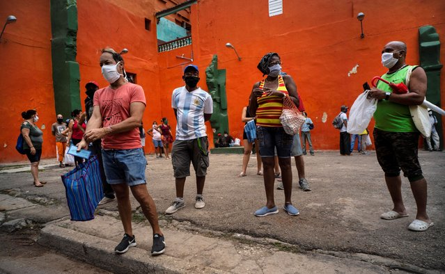 Shoppers wearing protective face masks as a precaution against the spread of the coronavirus, wait their turn to enter a store to buy food, in Havana, Cuba, Wednesday, May 13, 2020. Cuban authorities are requiring the use of masks for anyone outside their homes amid the COVID-19 pandemic. (Photo by Ramon Espinosa/AP Photo)