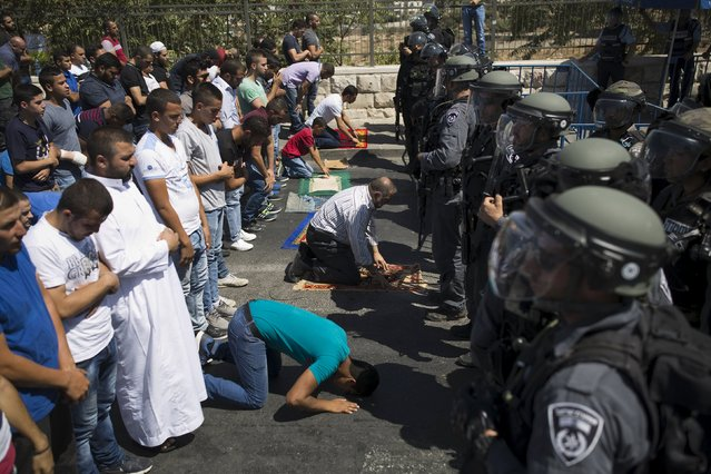 Palestinian men take part in Friday prayers outside the Old City as Israeli police officers stand guard in Arab east Jerusalem neighbourhood of Wadi al-Joz September 18, 2015. (Photo by Ammar Awad/Reuters)