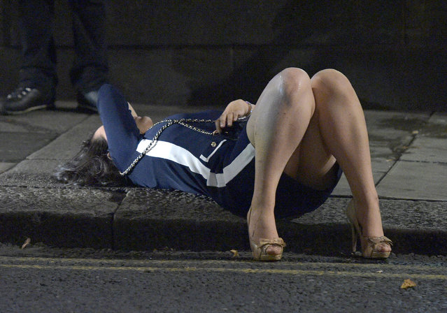 A scantily-clad brunette is pictured passed out on the pavement. Mayhem hits the streets of Newcastle, UK as clubbers out on the Toon have a little too much to drink as they enjoy the Bank Holiday on August 29, 2016. Photographs take last night show scantily-clad women passed out on the pavement, while boozed-up men were caught arguing with police. (Photo by XposurePhotos.com)