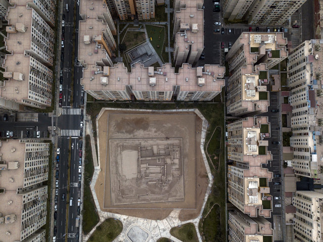 In this September 4, 2017 photo, high-rise apartment buildings surround the Huantinamarca pre-Columbian archeological site, along Pacifico Avenue in Lima, Peru. A small group of archeologists and officials are stepping up efforts to preserve the sites being squeezed by urban sprawl. (Photo by Rodrigo Abd/AP Photo)