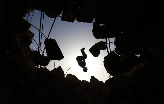 """A young Syrian man performs a """"parcours"""", an obstacle course method derived from military training, over the ruins of a building destroyed during past shelling by pro-regime forces, in the town of Binnish in the country's northwestern Idlib province, on June 17, 2020. (Photo by Abdulaziz Ketaz/AFP Photo)"""