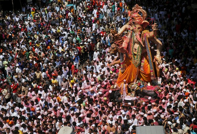 Devotees pull an idol of Hindu god Ganesh, the deity of prosperity, through a street on the last day of the ten-day-long Ganesh Chaturthi festival in Mumbai, India, September 27, 2015. (Photo by Shailesh Andrade/Reuters)