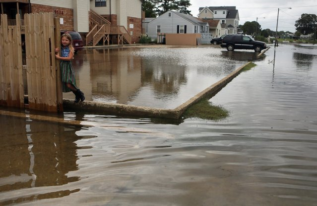 Chloe Riffle, 7, watches as she is surrounded by water on Sunday, September 4, 2016 in the Ocean View section of Norfolk, Va.  Storm system Hermine spun away from the U.S. East Coast on Sunday, removing the threat of heavy rain but maintaining enough power to churn dangerous waves and currents – and keep beaches off-limits to disappointed swimmers and surfers during the holiday weekend. (Photo by Vicki Cronis-Nohe /The Virginian-Pilot via AP Photo)