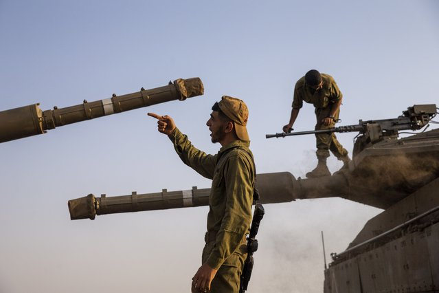 """Israeli soldiers work on tanks in the Israeli controlled Golan Heights near the border with Syria, not far from Lebanon border, Tuesday, July 28, 2020. Lebanon's prime minister has accused Israel of provoking a """"dangerous escalation"""" along the border in an attempt to modify the mandate of a U.N. peacekeeping force in south Lebanon. (Photo by Ariel Schalit/AP Photo)"""