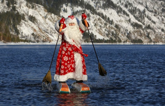 Nikolai Vasilyev, 64, dressed as Father Frost, the Russian equivalent of Santa Claus, water-skis along the Yenisei River outside the Siberian city of Krasnoyarsk, Russia December 19, 2017. Vasilyev, former teacher of the Siberian State Aerospace University, constructed the water skis out of plastic foam and designed the sticks to propel him forward, while travelling on the water surface. (Photo by Ilya Naymushin/Reuters)