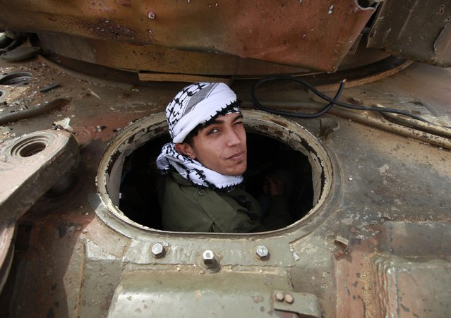 A rebel looks out of a destroyed tank belonging to pro-Gaddafi forces, at the western outskirts of Ajdabiyah, Libya, April 7, 2011. The rebel and his friends were smoking marijuana in the tank. (Photo by Andrew Winning/Reuters)