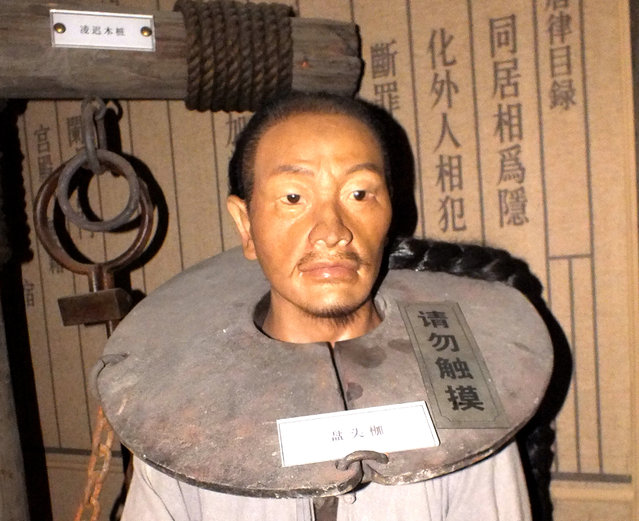 Wax figure with torture instrument is seen on October 25, 2014 in Huai'an, Jiangsu province of China. Exhibition of torture instruments was held by Huai'an government agency in Huai'an on Saturday to help people understand and study the history of ancient times. (Photo by ChinaFotoPress)