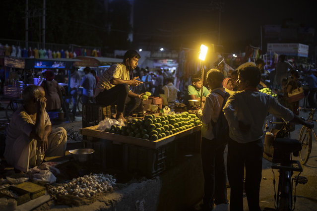 A roadside fruit vendor speaks to his customers, all without masks, at a daily evening market in Noida, on the outskirts of New Delhi, India, Thursday, July 16, 2020. As India's coronavirus caseload approaches 1 million, lockdowns are being reimposed in parts of the country as governments try to shield the health system from being overwhelmed. (Photo by Altaf Qadri/AP Photo)
