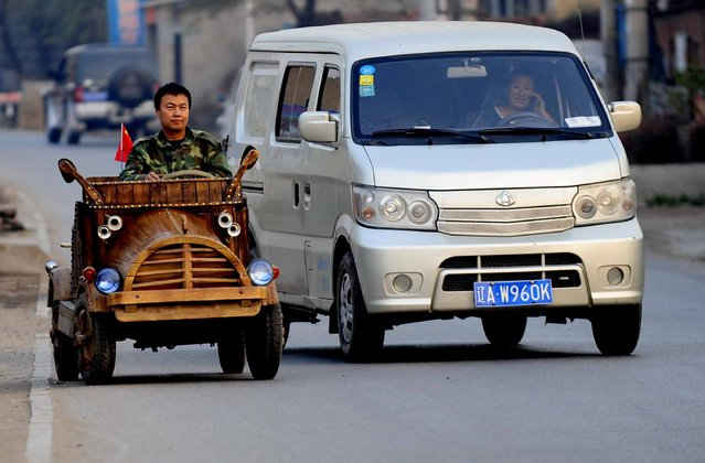 This picture taken on October 29, 2014 shows 48 years old carpenter Liu Fulong (L) driving a wooden car made by himself on a street in Shenyang, northeast China's Liaoning province. Liu Fulong, who stopped his education after primary school, spent more than 3 months on this wooden electric car that could travel at full speed 30 km per hour when fully charged, local media reported. (Photo by AFP Photo)