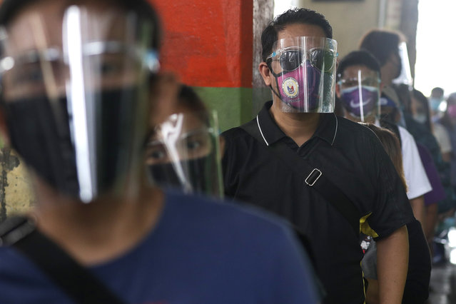 People wearing face mask and face shields to help curb the spread of COVID-19 line up for a bus ride in Caloocan city, Philippines on Wednesday, August 19, 2020. Philippine President Rodrigo Duterte has decided to ease a mild coronavirus lockdown in the capital and four outlying provinces to further reopen the country's battered economy despite having the most reported infections in Southeast Asia. (Photo by Aaron Favila/AP Photo)