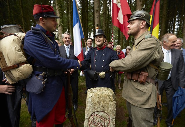 Military enthusiasts dressed as World War I soldiers (L-R French, Swiss and German) shake hands above a marker during a re-enactment in Le Largin near Bonfol in the Jura July 20, 2014. Le Largin, where Germany, France and Switzerland met in 1914, was the kilometre zero mark of the Western Front during WWI. (Photo by Denis Balibouse/Reuters)