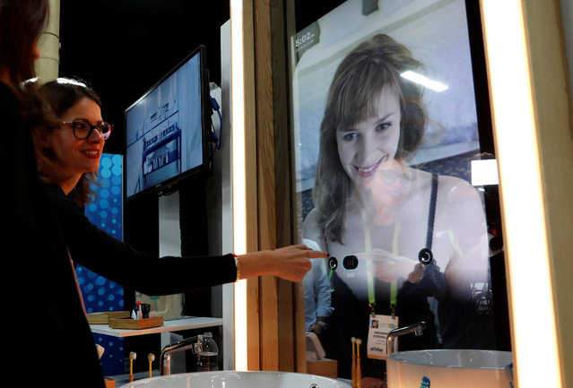 A woman demonstrates the features of a Care OS smart health and beauty hub in a mirror, during CES Unveiled at the 2018 CES in Las Vegas, Nevada, U.S. January 8, 2018. (Photo by Steve Marcus/Reuters)