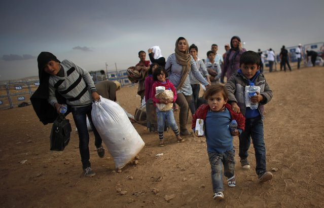 Kurdish Syrian refugees carry their belongings after crossing the Turkish-Syrian border near the southeastern town of Suruc in Sanliurfa province in this September 25, 2014 file photo. (Photo by Murad Sezer/Reuters)
