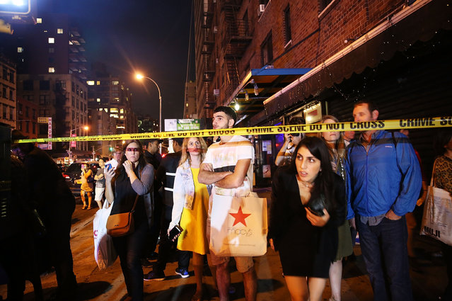 People stand behind police lines as firefighters, emergency workers and police gather at the scene of an explosion in Manhattan on September 17, 2016 in New York City. The evening explosion at 23rd street in the popular Chelsea neighborhood injured over a dozen people and is being investigated. (Photo by Spencer Platt/Getty Images)