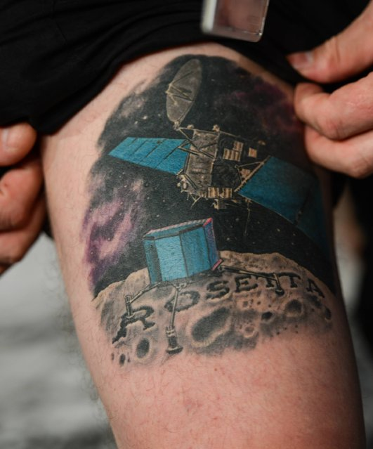 "In this   November 12, 2014  picture ESA  physicist  Matt Taylor shows his ""Rosetta"" tattoo at the satellite control center of the European Space Agency (ESA) in Darmstadt, Germany.  British physicist Matt Taylor brimmed with excitement as the European Space Agency's Philae lander successfully separated from the Rosetta spacecraft, showing off a colorful tattoo on his thigh of both, while proclaiming ""we're making history"". (Photo by Arne Dedert/AP Photo/DPA)"