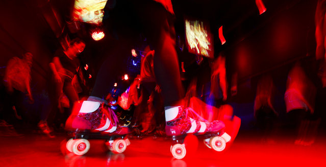 """People dance at the """"Roller Skate Disko"""" at the club SO36 in Berlin, Germany, September 5, 2016. SO36, which is located in Berlin's Kreuzberg district, made its name as a punk venue, and now hosts a variety of music and events. (Photo by Hannibal Hanschke/Reuters)"""