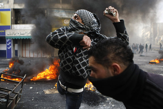 A Palestinian protester throws stones during clashes with Israeli soldiers in the West Bank city of Hebron following the funeral of Palestinian prisoner Arafat Jaradat, on  February 25, 2013. Jaradat's death in an Israeli jail on Saturday and a hunger strike by four other Palestinian inmates have raised tension in the occupied territory after repeated clashes between stone-throwers and Israeli soldiers in recent days. (Photo by Mussa Qawasma/Reuters)