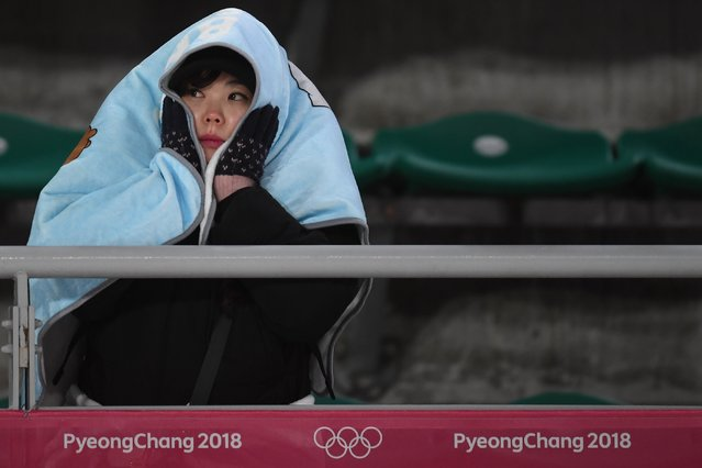 A woman sits in the cold as she attends the men' s normal hill individual ski jumping event during the Pyeongchang 2018 Winter Olympic Games on February 10, 2018, in Pyeongchang. (Photo by Christof Stache/AFP Photo)