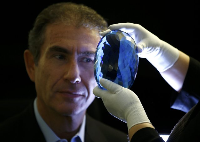 """Philanthropist Maurice Ostro looks through his Ostro stone, the largest known blue topaz stone, for media at the Natural History Museum in London, Britain September 27, 2016. The Ostro stone weighs around 2 kg (4.4 lb) and will be exhibited from Oct. 19, on permanent loan from British entrepreneur and philanthropist Maurice Ostro, the museum said. Its value was not disclosed. """"The original rough material that the gemstone was cut from was discovered three decades ago by British explorer Max Ostro in Minas Gerais, Brazil"""", it said in a statement. """"The Ostro stone is the largest cut topaz to go on show at the museum...It is an impressive 9,381 carats and will be displayed alongside specimens from one of the world's most important mineral collections"""". (Photo by Peter Nicholls/Reuters)"""