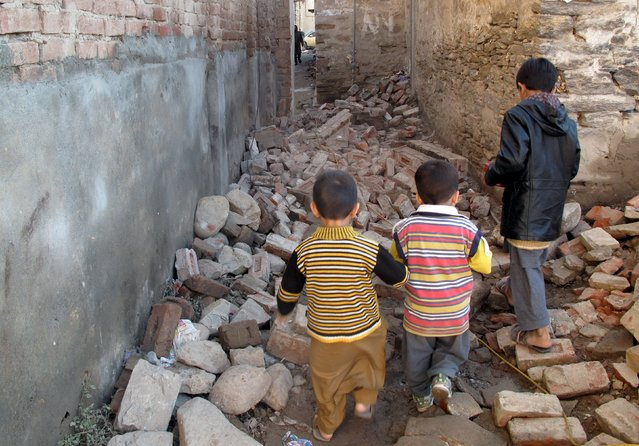 Children walk along a street with rubble from houses damaged by an earthquake in Mingora, Swat, Pakistan October 27, 2015. (Photo by Hazrat Ali Bacha/Reuters)