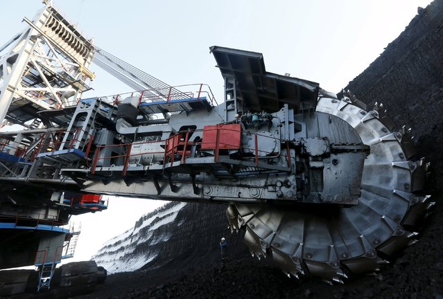 Master Sergey Suprun uses a portable radio set as he stands near a rotary dredge which works on the coal face of the Borodinsky opencast colliery, near the Siberian town of Borodino, east of Krasnoyarsk, Russia October 27, 2015. The Borodinsky colliery, 9 km (5.6 miles) long and more than 100 meters (328 feet) deep, annually produces more than 20 million tons of coal and is considered to be the biggest opencast coal mine in Russia, according to official representatives. (Photo by Ilya Naymushin/Reuters)