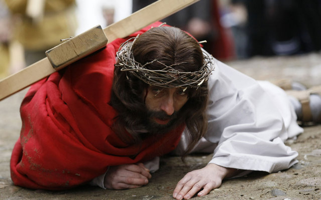 A man playing the role of Jesus carries a cross to the Church of the Holy Sepulchre on Good Friday during Holy Week, in the north of Poland March 29, 2013. (Photo by Kacper Pempel/Reuters)