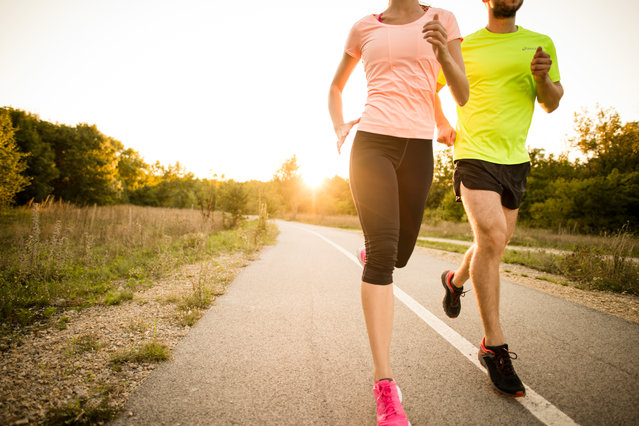 Detail of young people jogging together in nature with sun setting behind them. (Photo by Martin Novak/Getty Images)