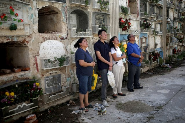 A family stands in front of the grave of a relative at the General Cemetery in Guatemala City October 31, 2015. (Photo by Jorge Dan Lopez/Reuters)