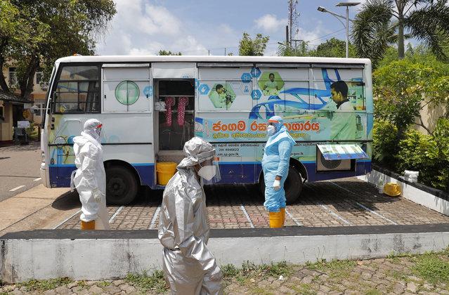 Sri Lankans health workers prepare to take swab samples of people to test for COVID-19 near a mobile testing vehicle outside a hospital in Minuwangoda, Sri Lanka, Tuesday, October 6, 2020. (Photo by Eranga Jayawardena/AP Photo)