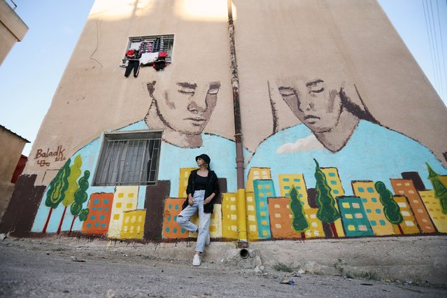 Jordanian artist, Maha Hindi, poses in front of her mural on a building as part of the Baladk festival, which includes murals across Amman all with a message encouraging people to protect the environment, Jordan, October 13, 2020. (Photo by Muhammad Hamed/Reuters)