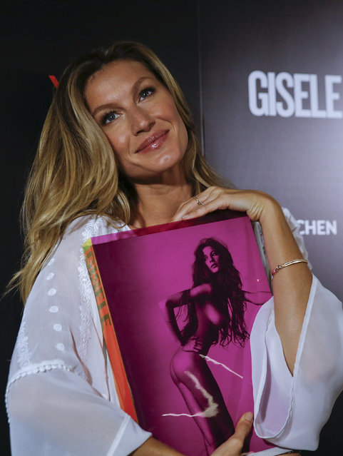 Brazilian model Gisele Bundchen poses for pictures with her book, titled Gisele Bundchen, dedicated her 20-year modeling career, prior to signing autographs in Sao Paulo, Brazil, Friday, November 6, 2015. (Photo by Andre Penner/AP Photo)