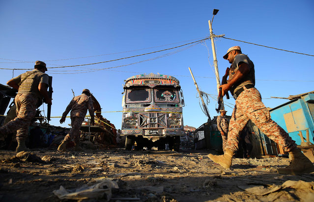 Pakistani security officials inspect the scene of a blast that targeted a passenger bus, in Karachi, Pakistan, 20 October 2020. At least six people were injured in a bomb explosion on a passenger bus in Karachi on 20 October. (Photo by Shahzaib Akber/EPA/EFE)