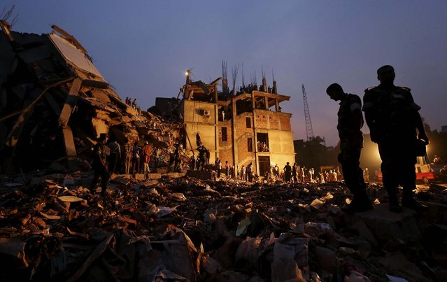 Soldiers stand in the rubble at the site of the building collapse. (Photo by Kevin Frayer/Associated Press)