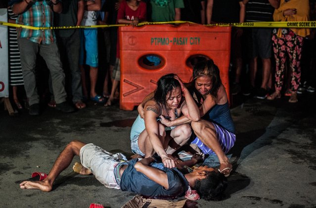 Two women cry in grief after armed assailants in a motorcycle shot their loved one in a main thoroughfare on July 23, 2016 in Manila, Philippines. The victim was an alleged drug peddler a claim disputed by his wife and maintained her husband is nothing more than a pedicab driver plying his trade when he was shot in front of her. Philippine President Rodrigo Duterte declared a war on crime and drugs after winning the presidential elections on May 9, 2016. President Duterte has recently been living up to his nickname, 'The Punisher', as Philippine police have been conducting night time drug raids on almost a daily basis. With reports of at least 300 drug related deaths since the start of July, Human rights groups and the Catholic church have objected to the use of brutal force by the Police. (Photo by Dondi Tawatao/Getty Images)