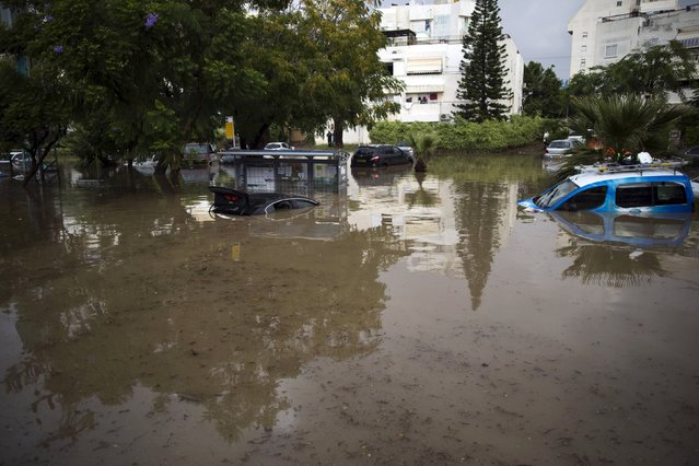 Vehicles are partially submerged in water on a flooded street in the southern city of Ashkelon, Israel, November 9, 2015. (Photo by Amir Cohen/Reuters)