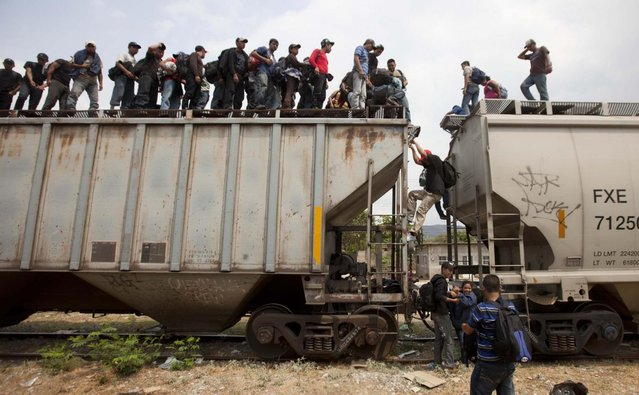 Migrants climb off a train during their journey toward the U.S.-Mexico border in Ixtepec, Mexico, Monday, April 29, 2013. Migrants crossing Mexico to get to the U.S. have increasingly become targets of criminal gangs who kidnap them to obtain ransom money. (Photo by Eduardo Verdugo/AP Photo)