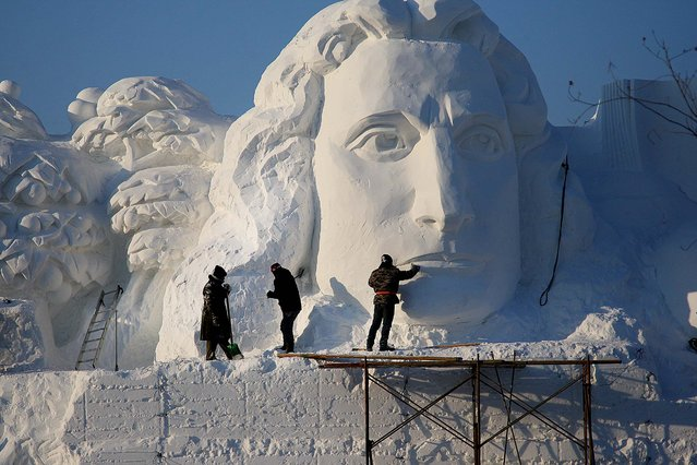 Workers put the finishing touches on a sculpture for the 27th Harbin Sun Island International Snow Sculpture Art Expo in Harbin, China, on December 20, 2014. (Photo by ChinaFotoPress/Getty Images)